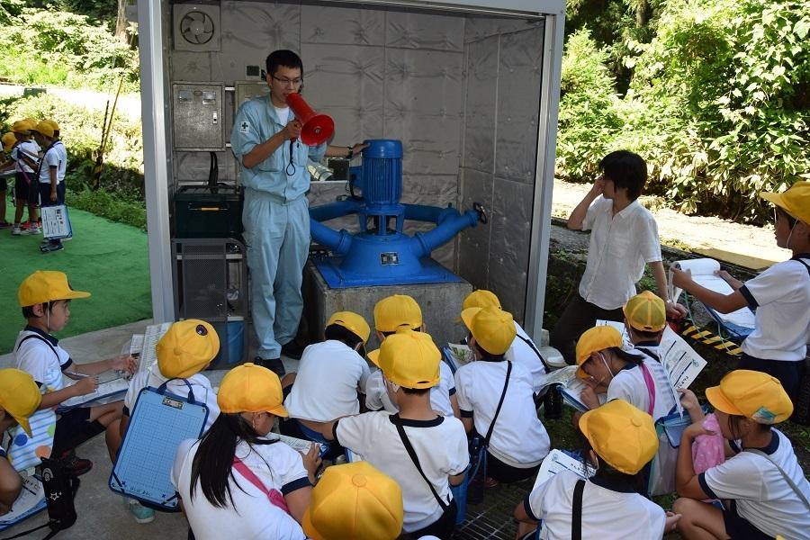 地元の小学生に小水力発電機を説明する